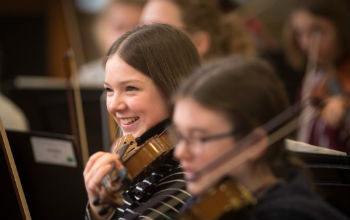 girls smiling in an orchestra