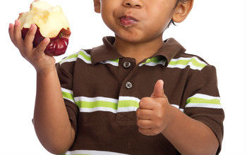 small boy eating an apple