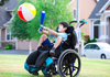 A child in a wheelchair witha a bat and ball.
