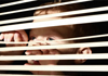 A child looking through a window blind.