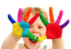 A child with hands decorated with primary colours.