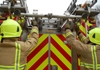 Two firefighters lifting a ladder from the rear of a fire appliance.