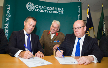 Three men sitting at a desk in front of an Oxfordshire County Council banner