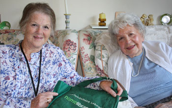 two ladies with a home library service bag