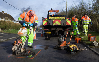 workmen fix a pothole