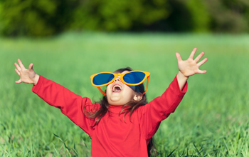 girl waving her arms in a field wearing sunglasses