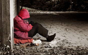 a homeless woman sitting by a wall