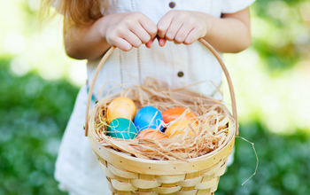 girl holding basket of chocolate eggs