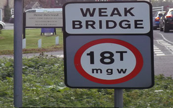 A road sign warning of a weak bridge.