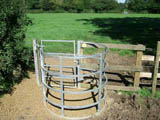 Picture of a metal kissing gate with sandy surface underneath, in the sun