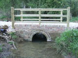 Picture of a neat stone bridge over stream with wooden railing