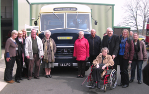 A group of older people next to a vintage bus