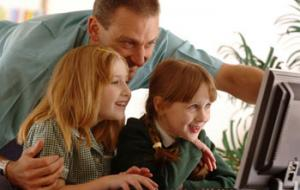 man and two girls looking at a computer
