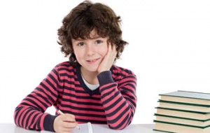 Boy writing in book with stack of books next to him