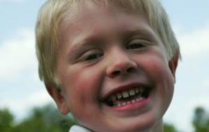 boy with blonde hair laughing