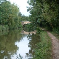 Stone towpath leading to arched bridge on the Oxford Canal
