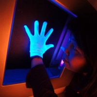 A gloved hand placed against a panel in the innovations gallery.