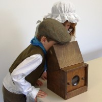 Two children use a camera obscura - The Marvels of Invention